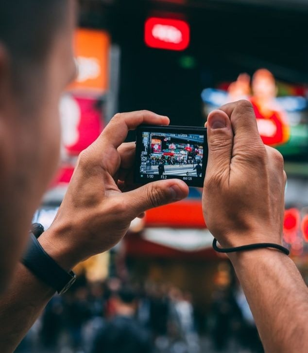 Un chinois prenant une photo avec son smartphone.