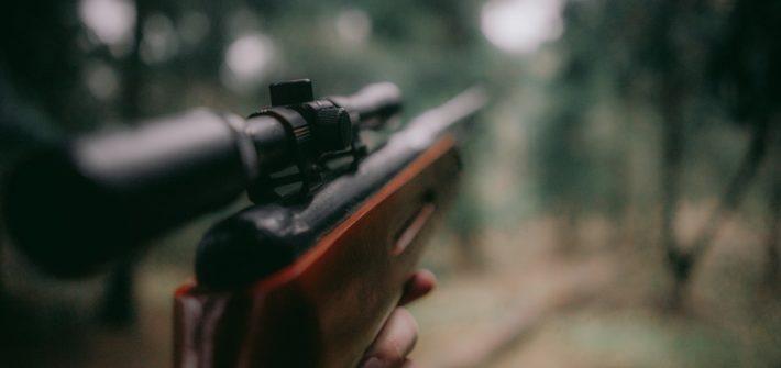 Un chasseur regardant dans le viseur de son fusil.